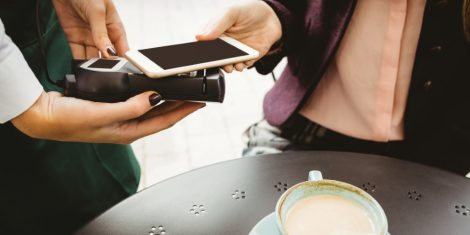 mastercard-mobilno-placevanje-1-Woman paying with mobile phone in cafe